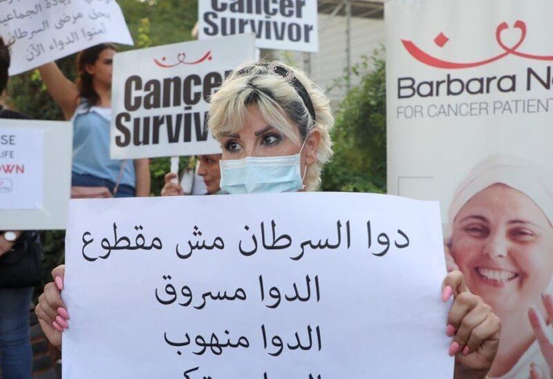 Christine Tohme, une patiente atteinte d'un cancer, tient un panneau lors d'un sit-in de protestation face à la pénurie de médicaments contre le cancer, devant le siège de l'ONU à Beyrouth, le 26 août 2021. (Reuters)
